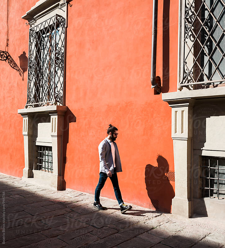 Man walking in front of an orange wall on a sunny day by Beatrix Boros for Stocksy United