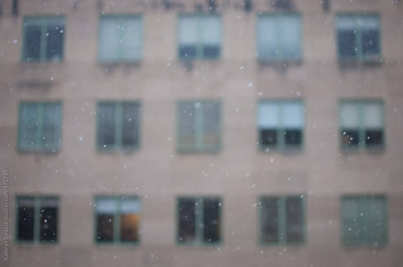 Snow falling in front of blurry building with lots of windows by Kathryn Swayze for Stocksy United
