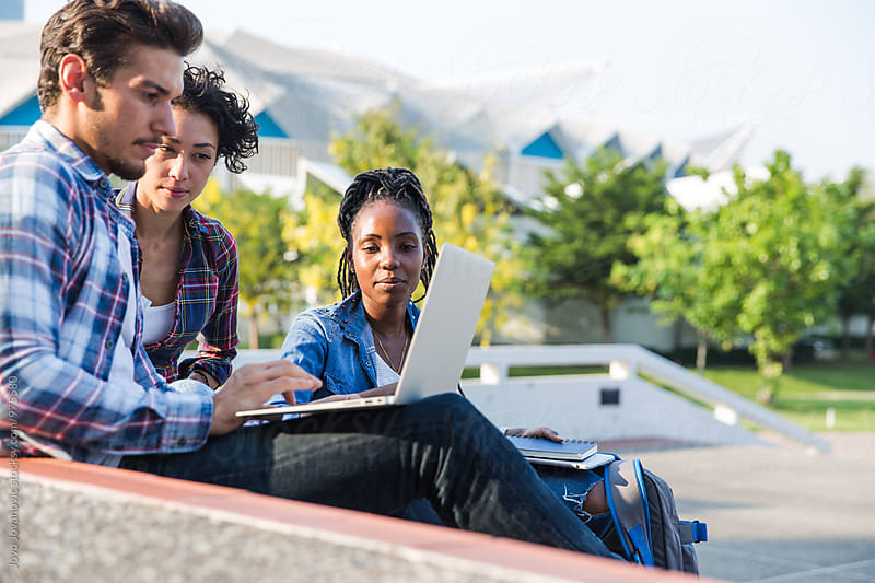 Three friend studying together outdoors with a laptop by Jovo Jovanovic for Stocksy United