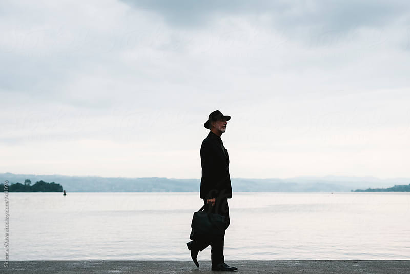 Gentleman walking against the lake by GIC for Stocksy United