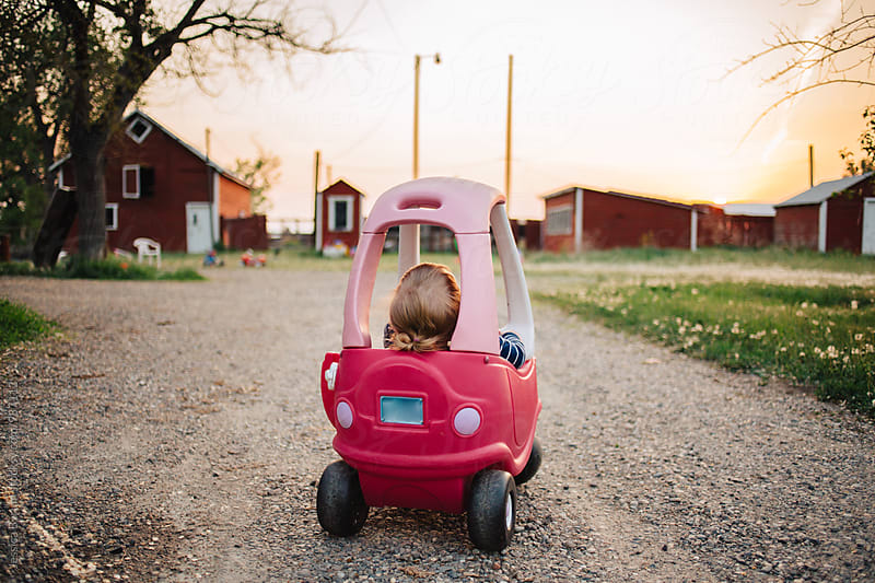 Toddler girl resting in a pink toy car at the end of the day. by Jessica Byrum for Stocksy United