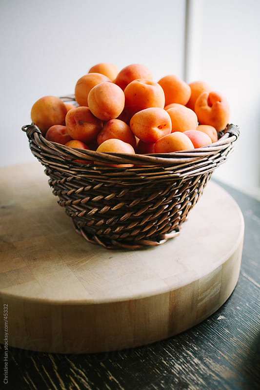 Fresh apricots sitting in a basket on a kitchen counter  by Christine Han for Stocksy United