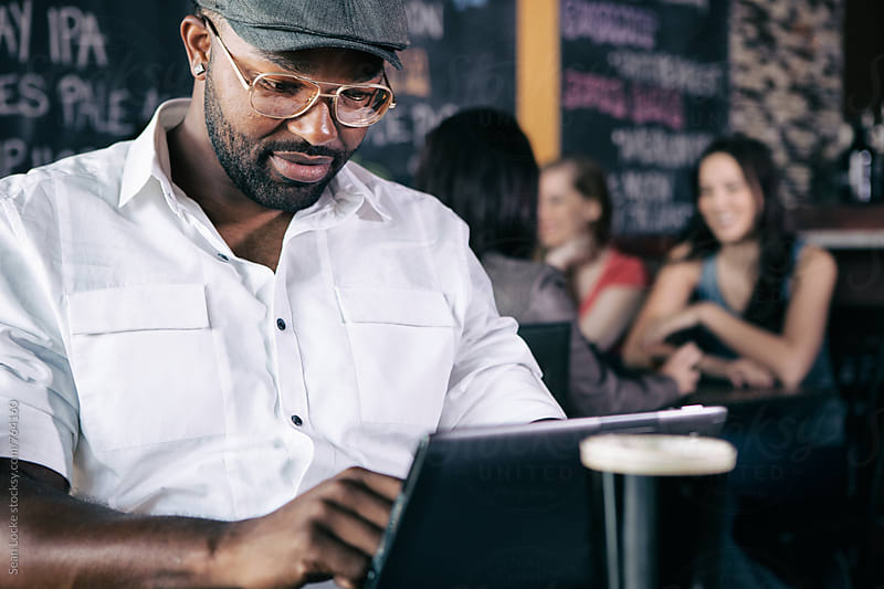 Bar: Man Working On Business In Bar On Digital Tablet by Sean Locke for Stocksy United