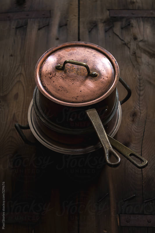 Old copper utensils on wooden table by Pixel Stories for Stocksy United