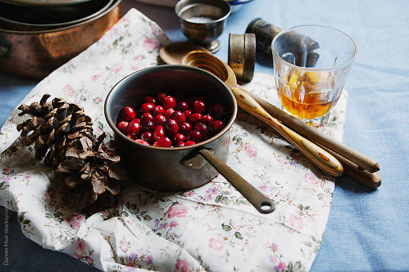 Cranberry's in a pot on a table with ingredients.  by Darren Muir for Stocksy United