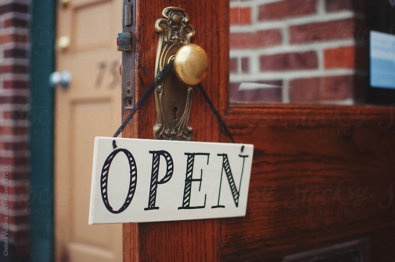 An open sign on a shop door by Chelsea Victoria for Stocksy United