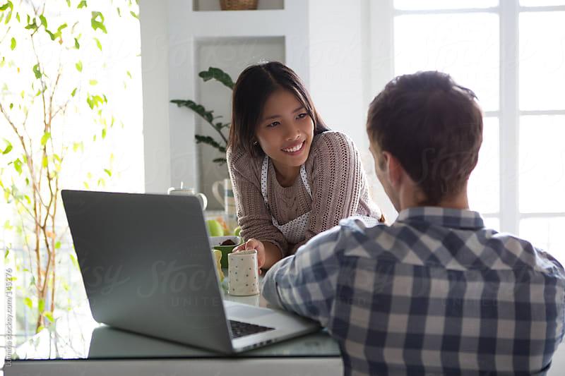 Smiling Couple Using Laptop by Lumina for Stocksy United