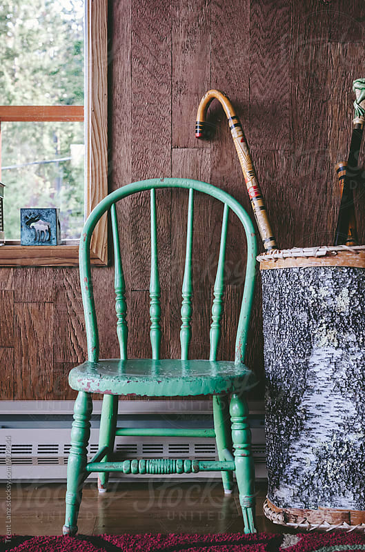Old green chair near basket with canes by Trent Lanz for Stocksy United
