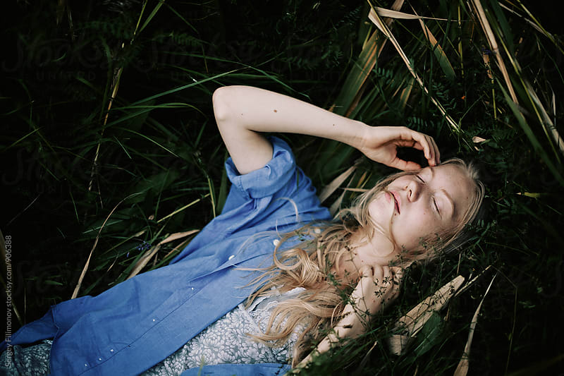 Portrait of the young blonde lying in a grass in the summer by Sergey Filimonov for Stocksy United