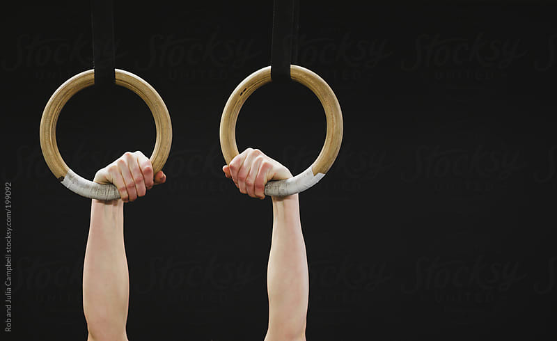 Hands holding onto rings in  gym by Rob and Julia Campbell for Stocksy United