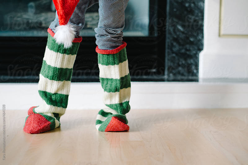 child wears Christmas stockings  by Tara Romasanta for Stocksy United