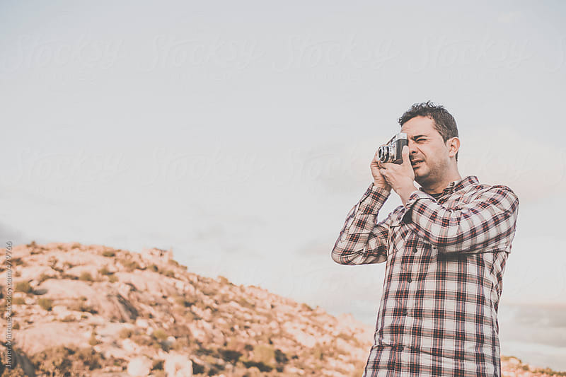 Man taking pictures in the mountains by Javier Márquez for Stocksy United