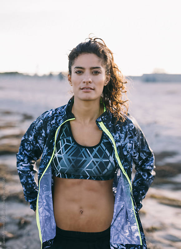 Woman in sportswear on beach by Jacob Lund for Stocksy United