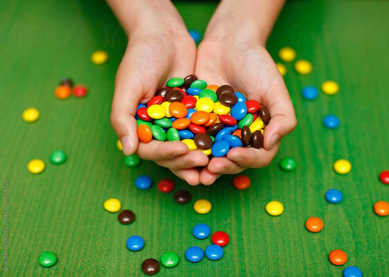 Boy holding colorful candys by Bratislav Nadezdic for Stocksy United