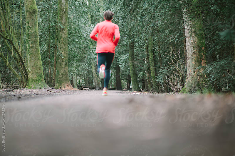 A runner running on a path through the forest by Ivo de Bruijn for Stocksy United