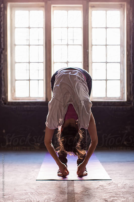 Woman bending over in a yoga flexibility exercise  by Jovo Jovanovic for Stocksy United