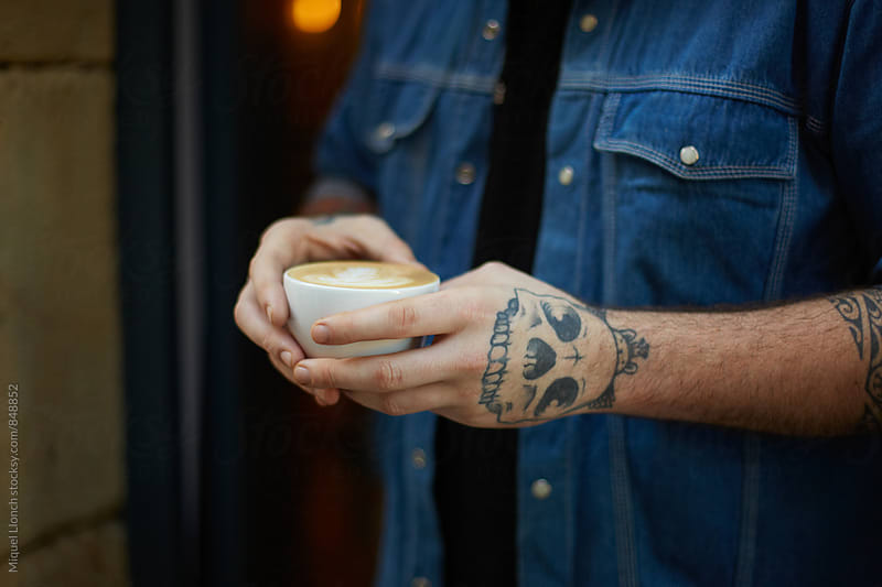 Close up of tattooed hands holding a cup of coffee by Miquel Llonch for Stocksy United