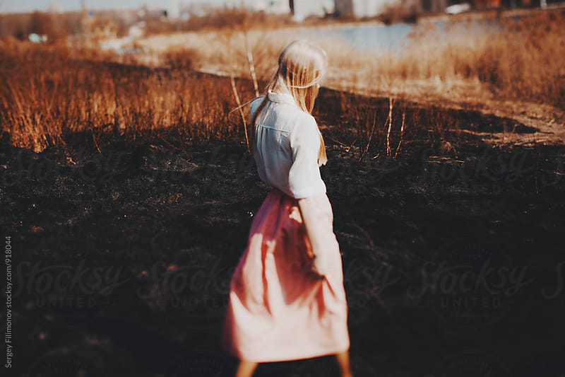 Blonde girl walks on the burned field by Sergey Filimonov for Stocksy United