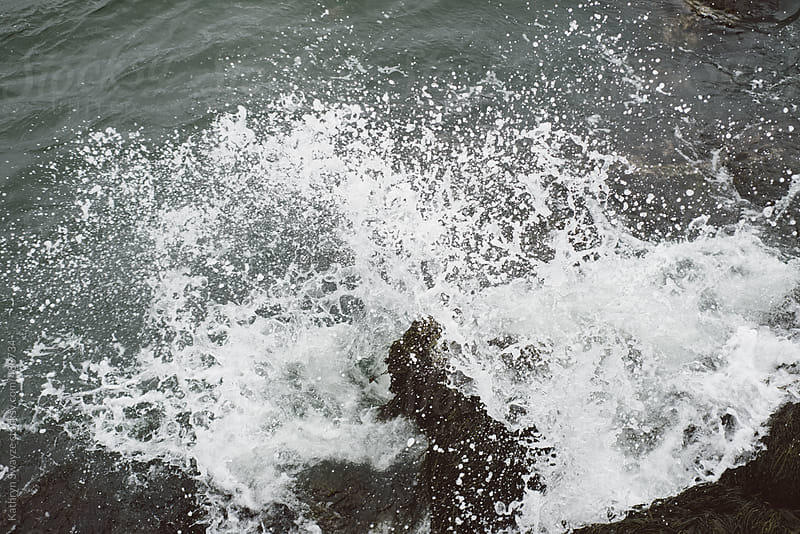 Ocean water crashing into seaweed covered rocks on a stormy day by Kathryn Swayze for Stocksy United