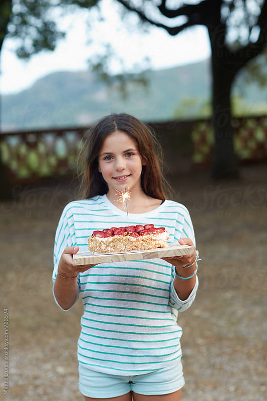 Young girl with a birthday cake by Miquel Llonch for Stocksy United