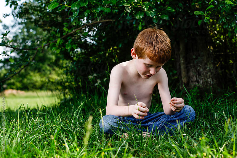 Young Redheaded boy sitting in grass without shirt by J Danielle Wehunt for Stocksy United