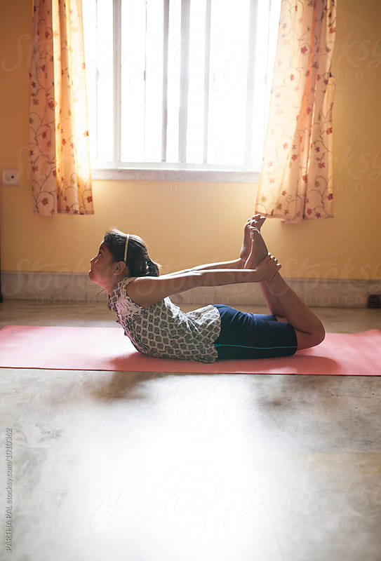 Teenage girl performing Yoga inside house by PARTHA PAL for Stocksy United