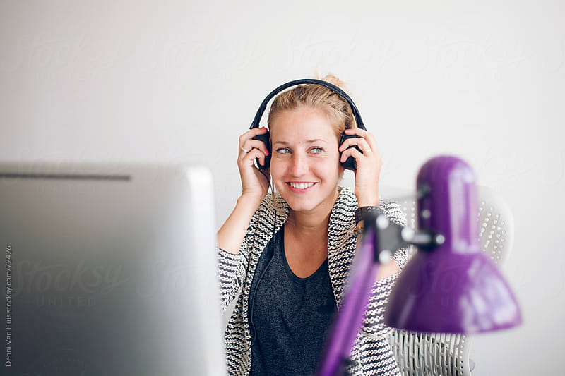 Blonde happy woman in an office working behind a desk using a computer wearing headphones   by Denni Van Huis for Stocksy United