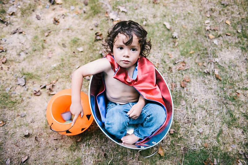 toddler in super hero cape waits for Halloween trick or treating by Tara Romasanta for Stocksy United
