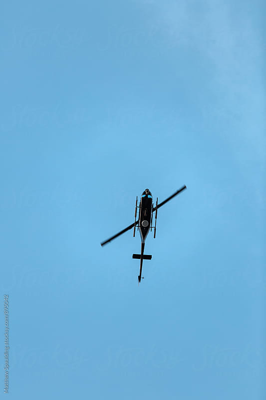 Helicopter hovering above in sky by Matthew Spaulding for Stocksy United