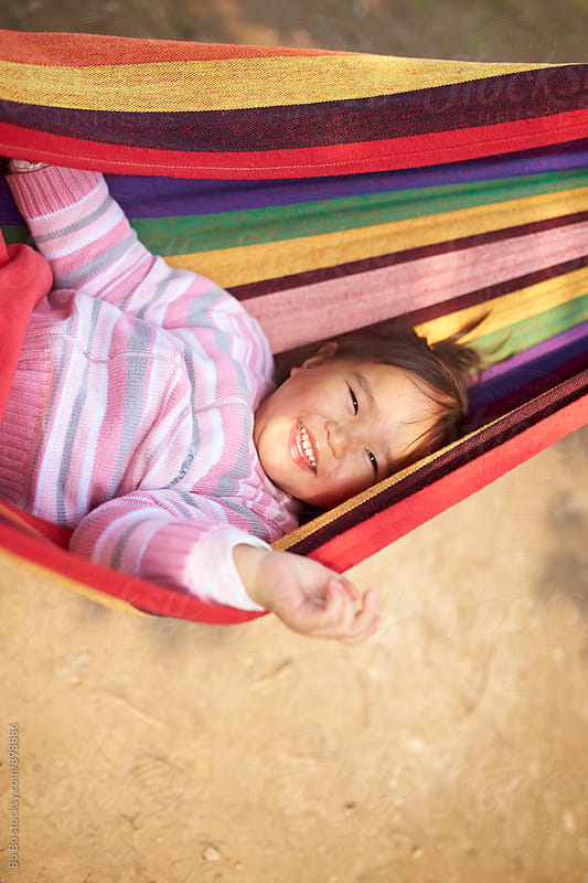 one happy little asian girl lying in hammock by cuiyan Liu for Stocksy United