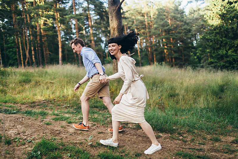 Young couple running along the forest road by Evgenij Yulkin for Stocksy United