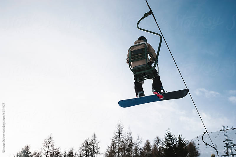 Man with snowboard on the chair lift by GIC for Stocksy United