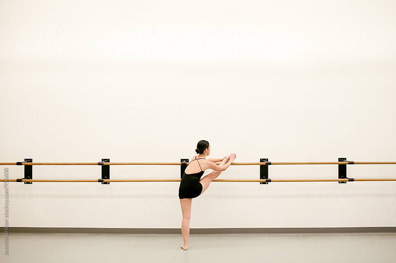 Graceful ballerina stretching  by Jennifer Brister for Stocksy United