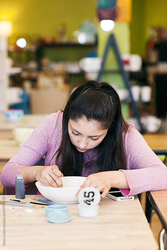 Teen Girl Sitting And Painting Interior Of Bowl by Sean Locke for Stocksy United