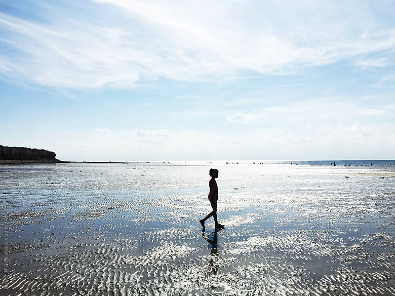 Silhouette of boy walking along beach by Kirstin Mckee for Stocksy United