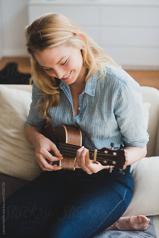 Young woman playing ukulele at home by Lauren Naefe for Stocksy United