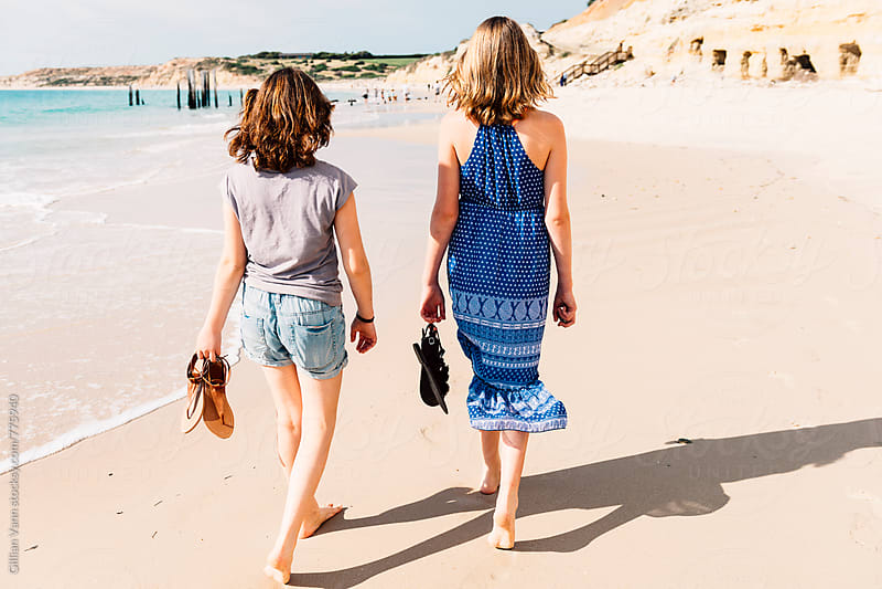two teenage girls walking along the beach, barefoot by Gillian Vann for Stocksy United