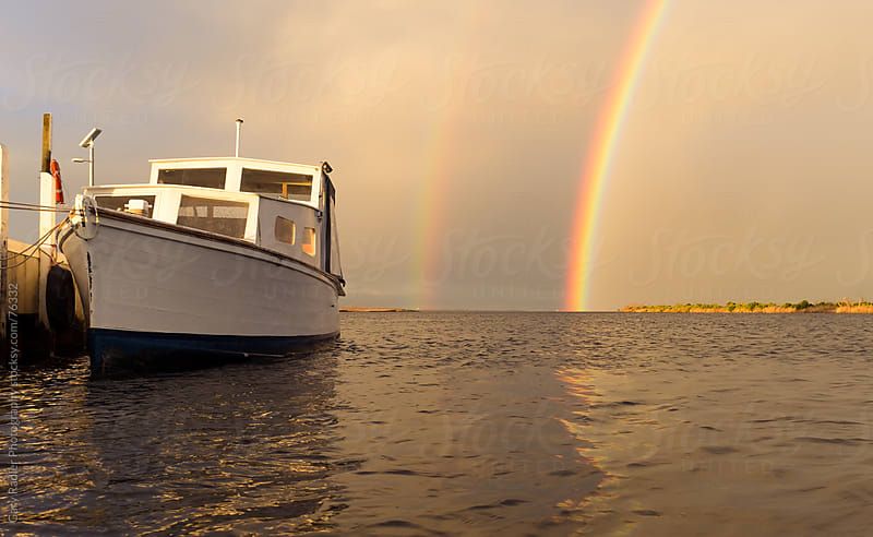 Boat in evening light against a double rainbow. by Gary Radler Photography for Stocksy United