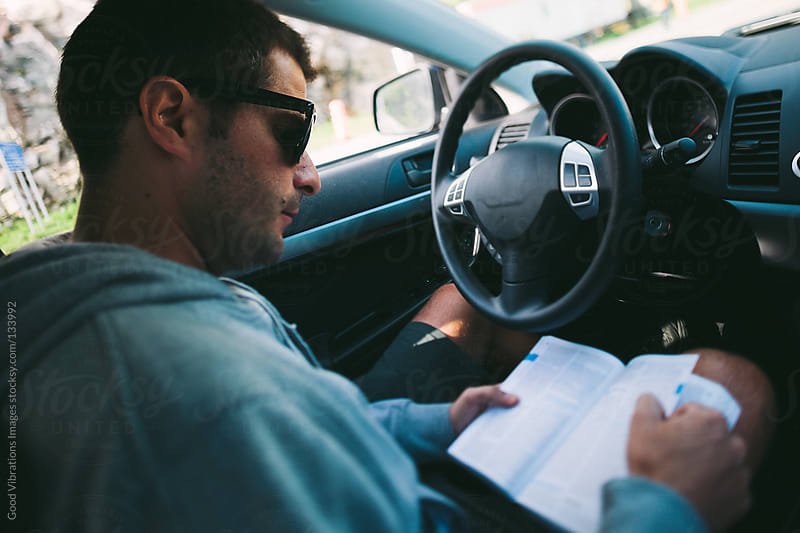 Man reading a guidebook in the car by Good Vibrations Images for Stocksy United
