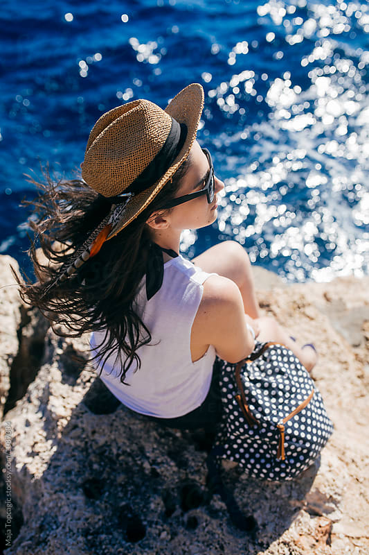 Beautiful fashionable woman sitting on the shore by Maja Topcagic for Stocksy United