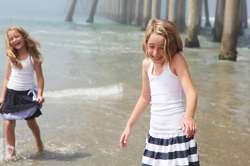Two Girls Playing At the Beach by the Pier by Dina Giangregorio for Stocksy United