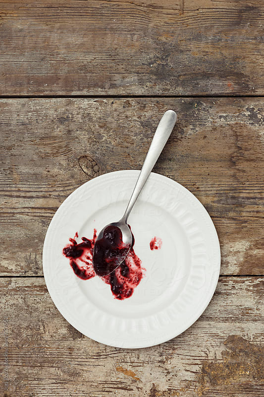 a spoon full of jam on a white plate by Juri Pozzi for Stocksy United