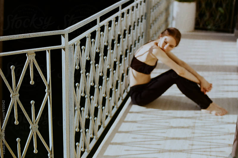 Woman sitting at a balcony in sunny day by Liubov Burakova for Stocksy United