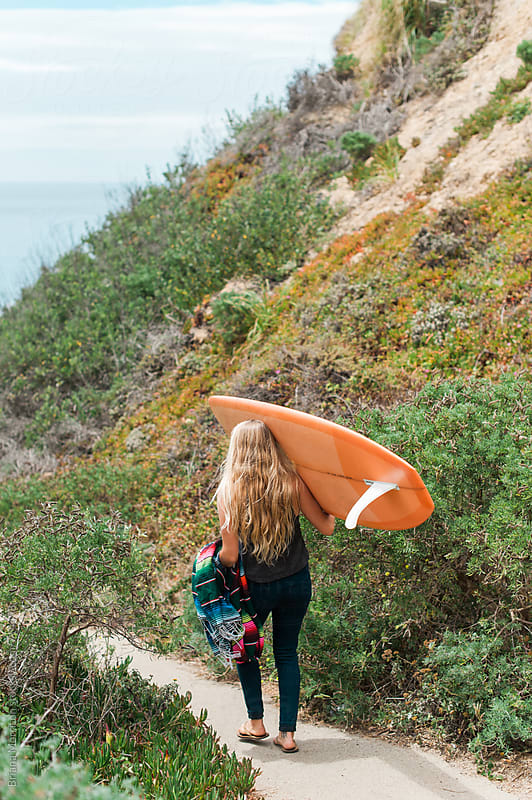 A Young Woman Viewed From Behind Carrying a Surfboard on a Path Towards the Ocean by Briana Morrison for Stocksy United