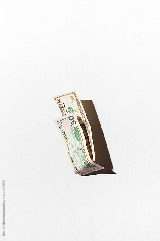 Dollar bills falling against a white wall. by Shikhar Bhattarai for Stocksy United