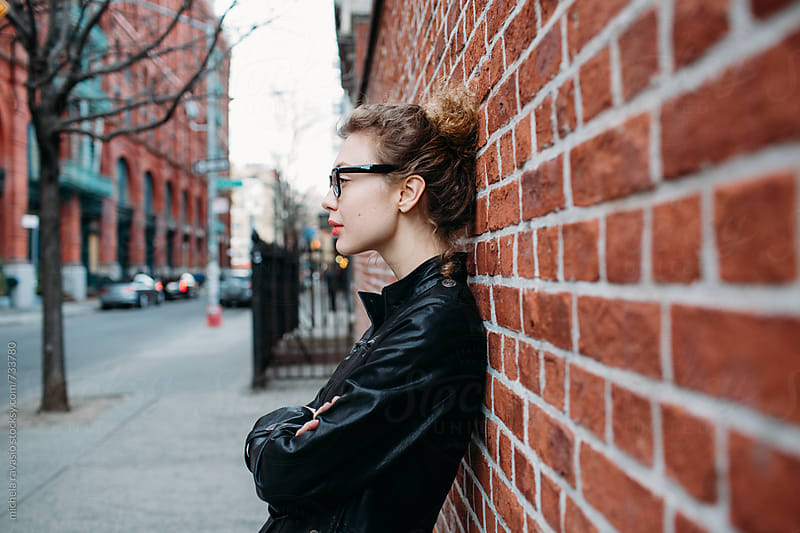 Profile of a beautiful woman leaning against a brick wall in NYC by michela ravasio for Stocksy United