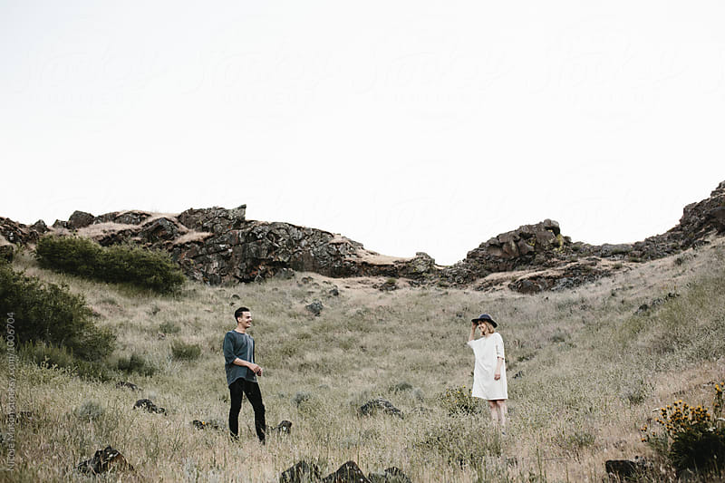 young fashionable couple standing distance apart in desert by Nicole Mason for Stocksy United