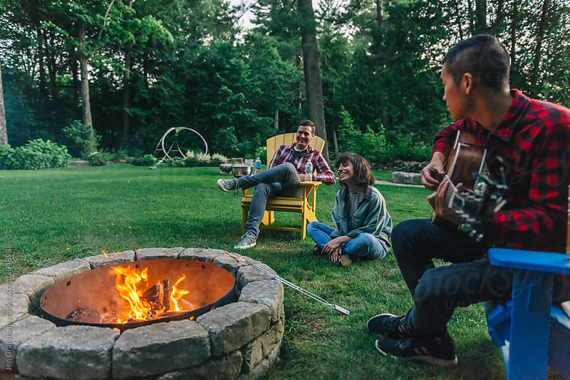 Friends roasting marshmallows around the campfire by Jen Grantham for Stocksy United