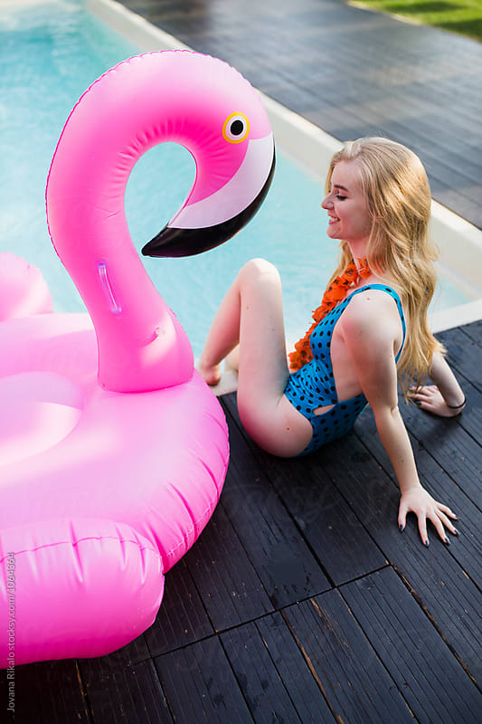 Young woman and a big flamingo float by Jovana Rikalo for Stocksy United