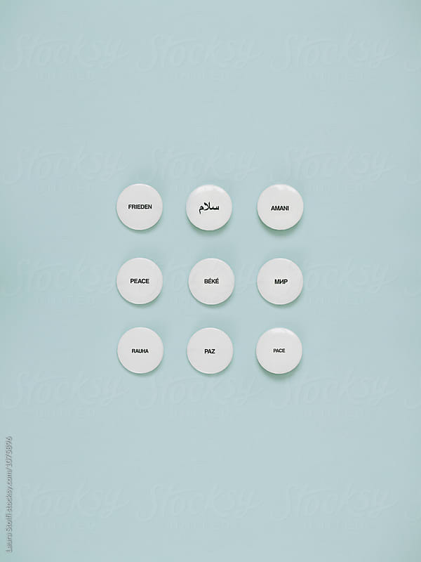 Pins spelling the word PEACE in multiple languages by Laura Stolfi for Stocksy United